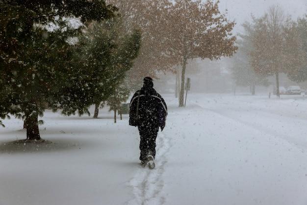 Personnage solitaire de l'homme sur une route enneigée pendant les chutes de neige en hiver