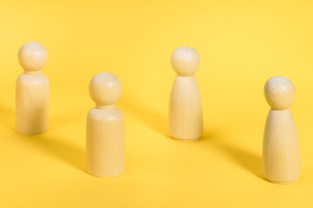 Les personnages en bois se tiennent sur fond jaune