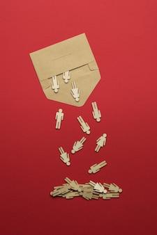 Des personnages en bois sortent d'une enveloppe postale en papier sur fond rouge. le concept de communication entre les personnes.