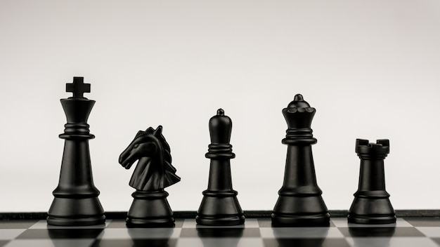 Personnages d'échecs noirs à bord.- idée commerciale de compétition. - concept de réussite et de leadership