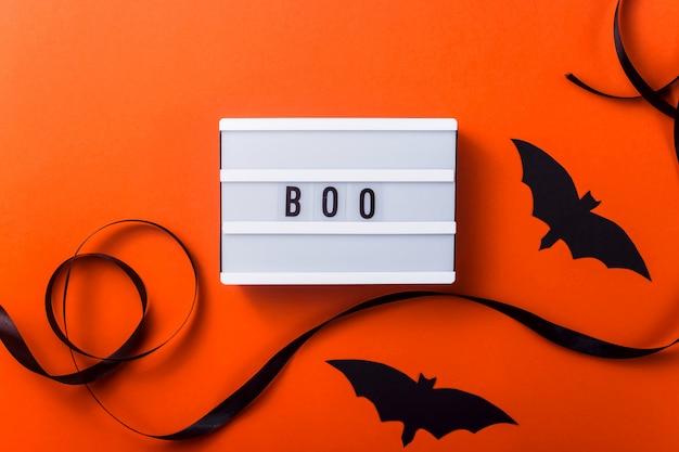 Personnages d'halloween noirs et accessoires sur une surface orange vif