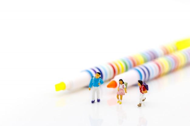 Personnages miniatures, enfants debout avec un stylo de couleur.