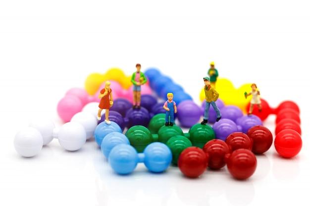 Personnages miniatures, enfants s'amusent avec des ballons colorés
