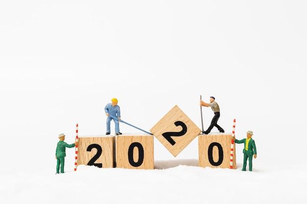 Personnages miniatures, une équipe de travailleurs crée un bloc de bois numéro 2020