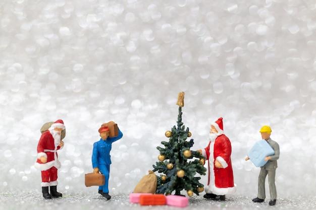 Personnages miniatures: une équipe de travailleurs prépare un arbre de noël