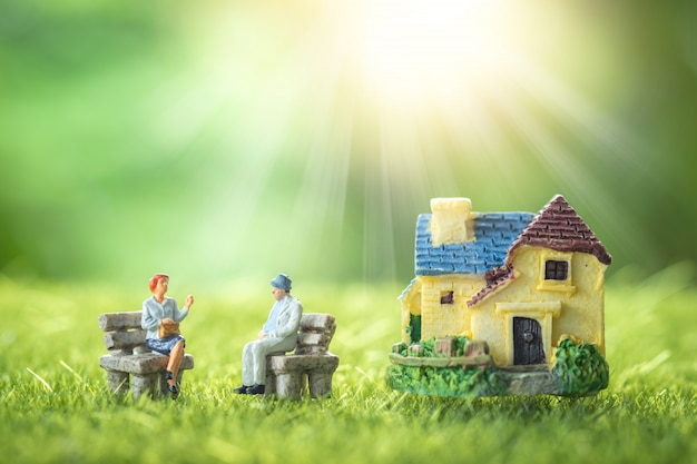 Personnages miniatures: heureux couple de personnes âgées assis devant une maison de retraite dans un jardin.