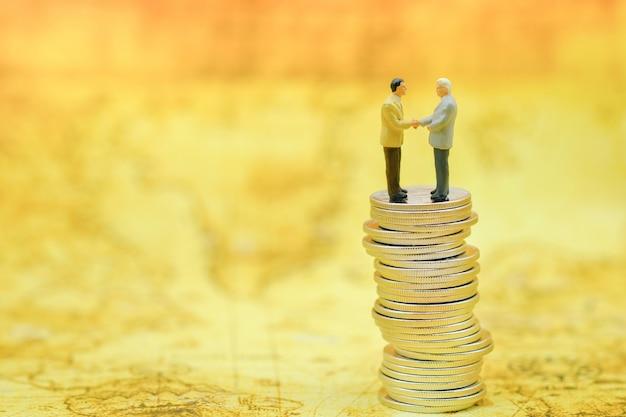 Personnages miniatures d'homme d'affaires parlant, serrer la main sur une pile instable de pièces de monnaie sur la carte du monde.