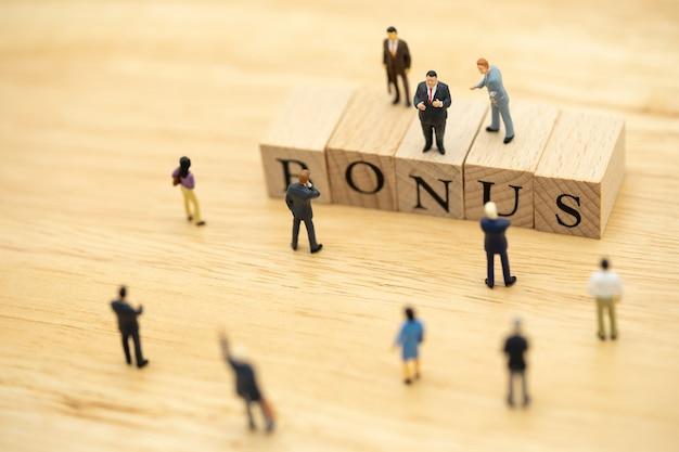 Personnages miniatures hommes d'affaires en attente de gains bénéfices de l'entreprise