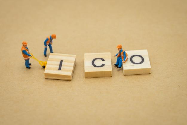 Personnages miniatures ouvrier du bâtiment réparant avec le mot bois ico (initial coin offer)
