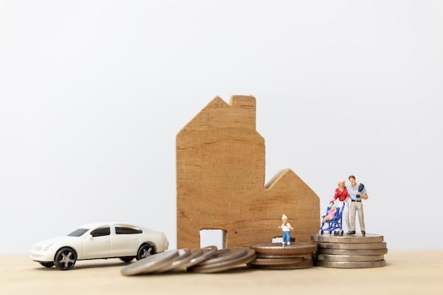 Personnages miniatures: parents avec enfants avec maison et pièces empilées