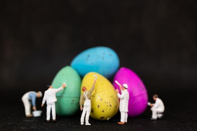 Personnages miniatures peignant des oeufs de pâques pour le jour de pâques