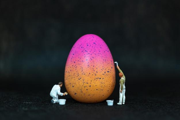 Personnages miniatures peignant des oeufs de pâques