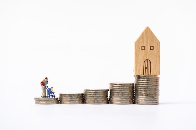 Personnages miniatures: un petit couple figure amoureux sur une pile de pièces avec le modèle de maison sur la pile du haut.