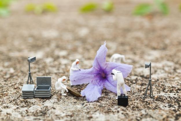 Personnages miniatures: police et détective découvrant la preuve d'une fleur sur une scène de crime