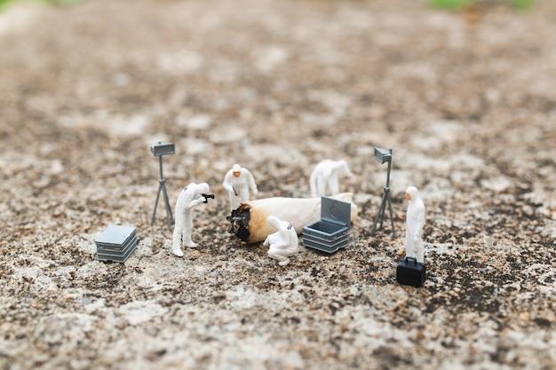 Personnages miniatures: police et détective découvrant la preuve d'une vieille cigarette sur une scène de crime