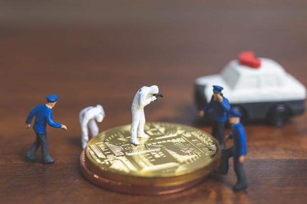 Personnages miniatures: police et détective devant le bitcoin crypto-monnaie
