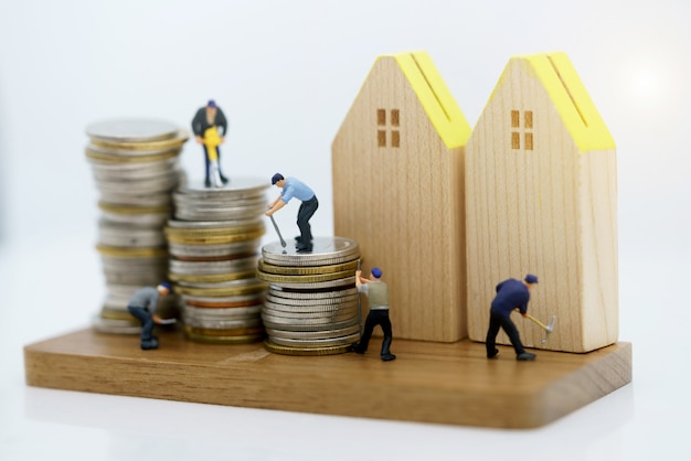 Personnages miniatures: les travailleurs travaillant avec des outils sur des pièces de monnaie empilent une maison en bois.