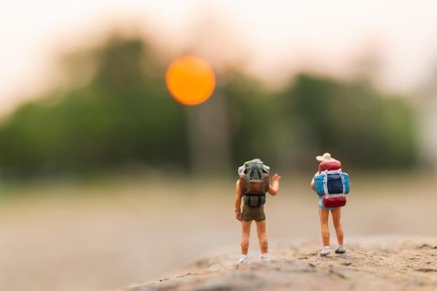 Personnages miniatures: voyageur avec sac à dos marchant sur le rocher