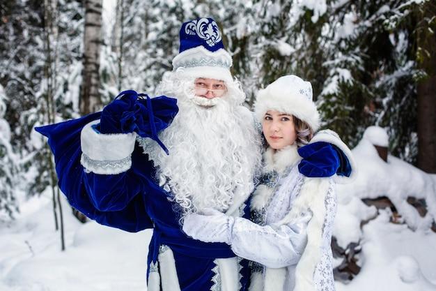 Personnages de noël russes ded moroz (père frost) et snegurochka (fille des neiges) dans une forêt enneigée.