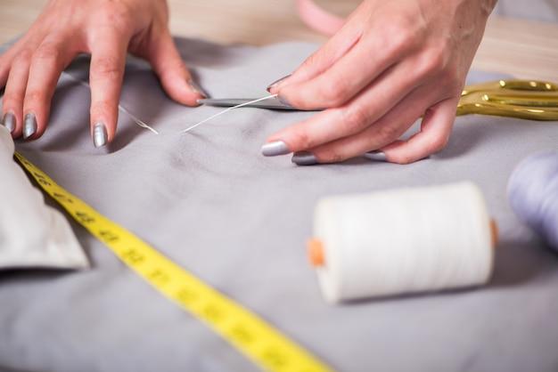 Personnaliser les mains travaillant sur de nouveaux vêtements