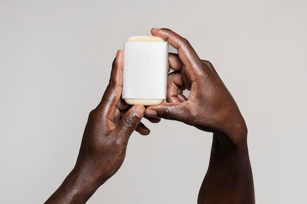 Personne africaine se laver les mains avec du savon isolé sur blanc