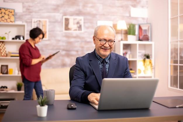 Personne âgée réussie en costume travaillant sur un ordinateur portable depuis la maison. sa femme est à l'arrière-plan