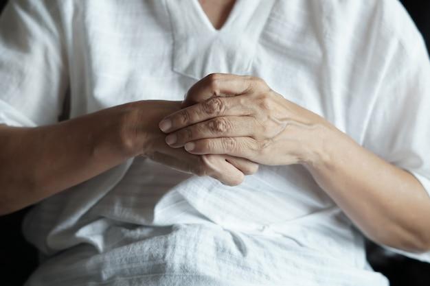 Personne âgée souffrant d'arthrite et femme âgée souffrant de douleur à la maison