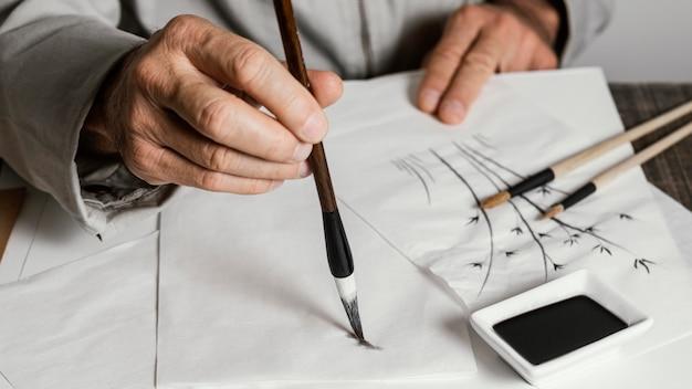 Personne à l'aide d'un pinceau d'encre chinoise sur papier blanc