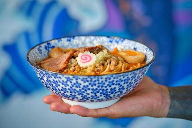 Personne anonyme tenant un bol de délicieuse soupe de nouilles asiatiques