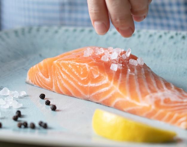 Une personne assaisonnant un filet de nourriture au saumon