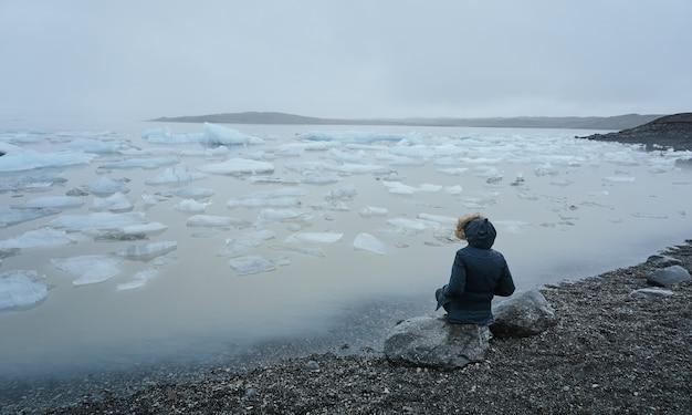 Personne assise sur un rocher au bord d'un lac de glace et entouré de brouillard en hiver. lac glaciaire de jokulsarlon
