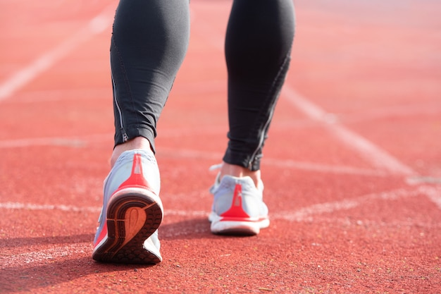 Personne athlétique sur la piste de course se prépare à commencer à courir
