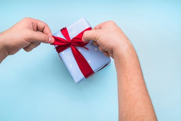 Une personne attachant le ruban sur la boîte cadeau enveloppée sur le fond bleu