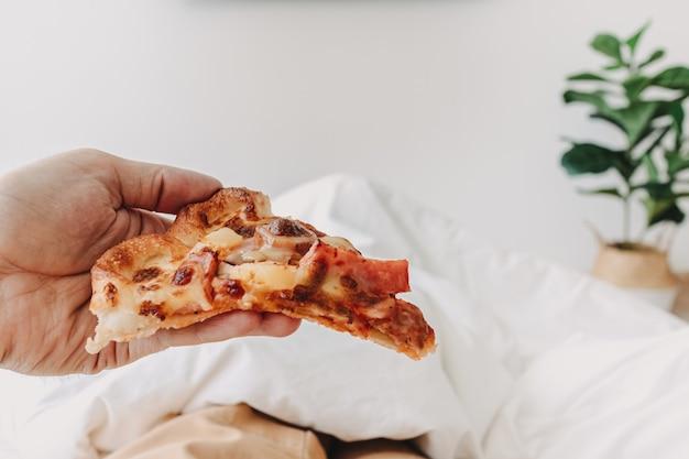 Une personne au lit avec une pizza regarde un concept télévisé de rester à la maison