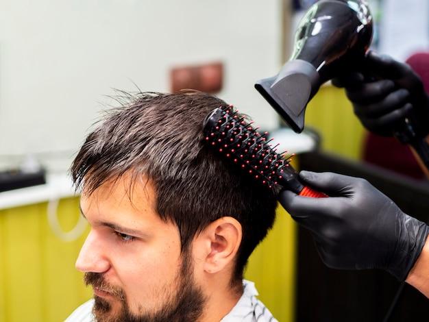 Personne ayant les cheveux séchés avec séchoir