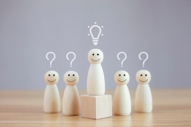 Une personne en bois heureuse modèle un smiley avec une idée parmi l'icône de points d'interrogation des personnes au visage triste