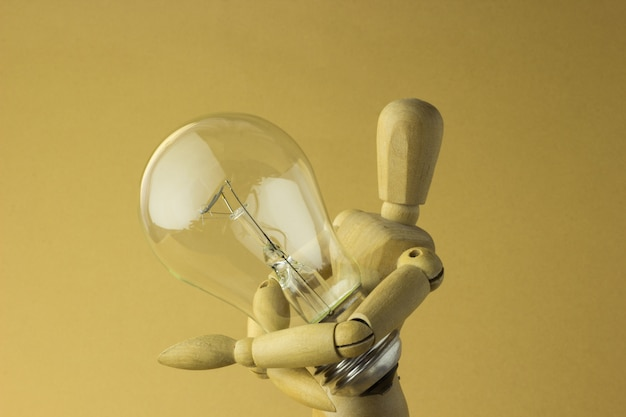 Personne en bois tient une ampoule électrique dans la main