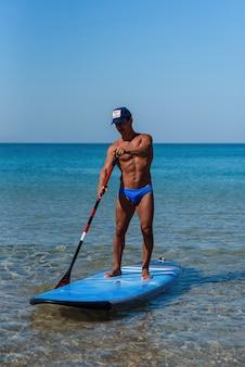 Une personne en bonne santé sportive se tient sur sa planche de surf sur l'eau, et ramant à la rame. le concept de style de vie sportif et sain.