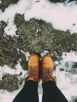 Personne en bottes avec un jean sur l'herbe verte près de la neige