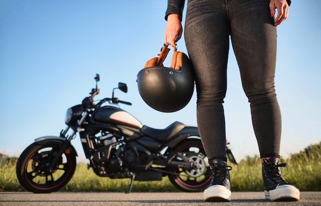 Personne avec casque à la main et moto