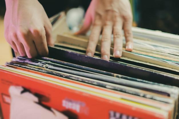 La personne choisit la collection de creusement de caisse de disque vinyle b