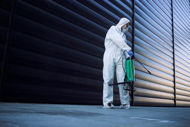 Personne en combinaison de protection chimique blanche faisant la désinfection des espaces publics pour arrêter la propagation du virus corona très contagieux