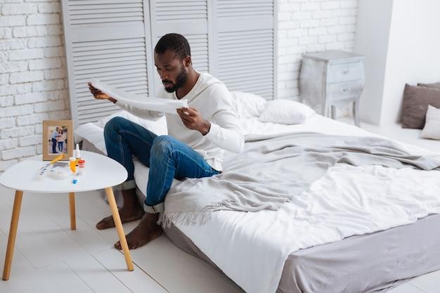 Personne concentrée. sérieux jeune homme calme à très concentré alors qu'il était assis sur un lit avec une serviette blanche dans les mains