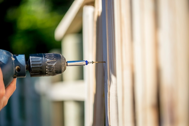 Personne construisant une clôture en bois avec une perceuse et une vis à l'aide d'une perceuse électrique à main dans un concept d'entretien de cour, de rénovations et de bricolage.