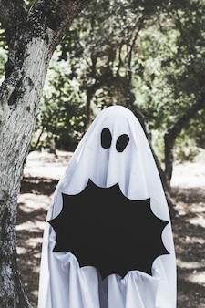 Personne en costume de fantôme tenant une décoration de halloween