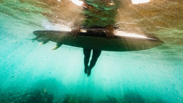 Personne couchée sur une planche de surf dans l'eau de mer bleue