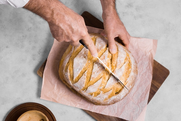 Personne coupant la moitié de la vue de dessus du pain