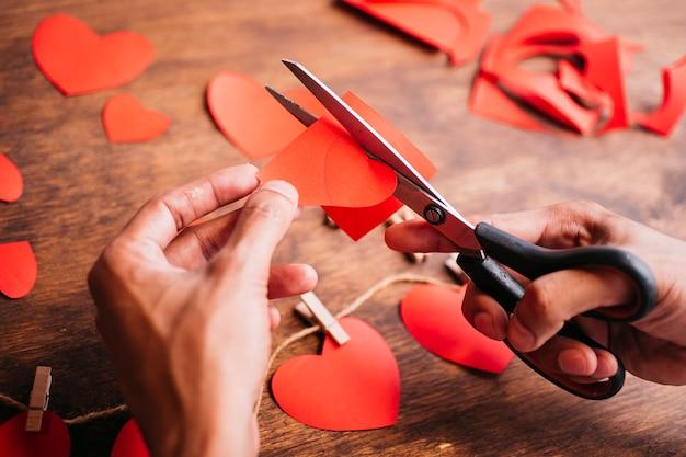 Personne coupe les coeurs de papier rouge