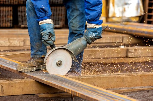 Une personne coupe une plaque d'acier