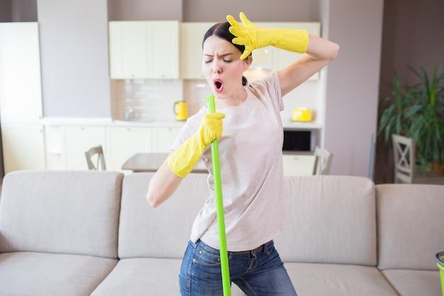 La personne créative se tient. elle chante et danse. fille tient la main gauche sur le front. la femme a un bâton vert dans la main droite. elle nettoie avec plaisir.